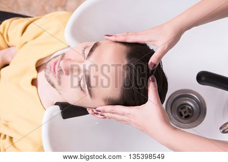 Young man lying with his eyes closed in beauty salon. Handsome man having his hair washed in hairdressing salon.