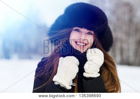 Portrait of young woman in fur hat in winter