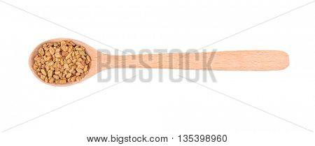 Fenugreek seeds in spoon on white background