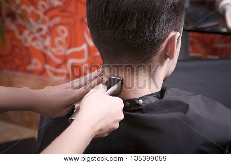 Closeup picture of man's hairstyling and haircutting with hair clipper in barber shop or hairdressing salon.