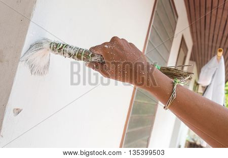 Painting walls.Painter paints using a brush,hand worker holding brush painting white on wall cement . (select focus brush to hold hand )