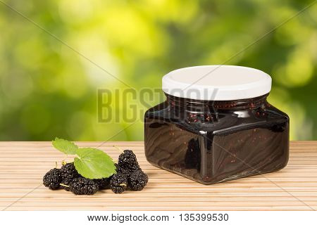 home made mulberry jam in jar and some fresh fruits and leaves on table green leaves background. Horizontal composition