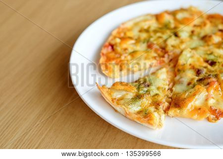 Hot pizza slice with melting cheese on wooden table
