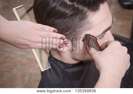 Fashion industry. Closeup picture man's hairstyling and haircutting with hair clipper by barber girl or hairdresser in barber shop or hairdressing salon.