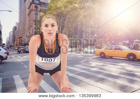 Tired athlete standing with hand on knee against new york street
