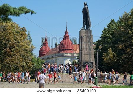 ORADEA, ROMANIA - AUGUST 01, 2015: children and kids playing summer games under the silhouette of the Unknown Soldier monument in 1 December Square; on background Faculty of Medicine built in 1869