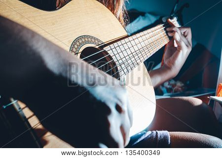 photography of woman's hands playing acoustic guitar close up