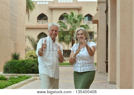 Amusing smiling senior couple with thumbs up on vacation