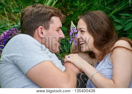 Young happy beautiful couple man and woman lying outdoors on the bright sunny day on green grass and looking at each other