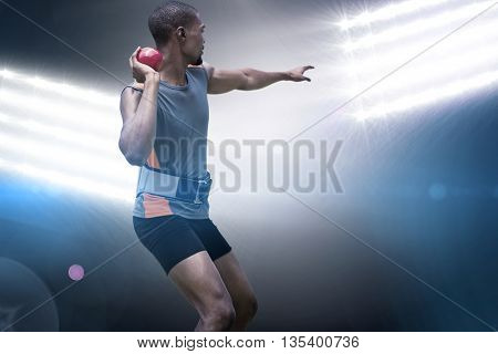 Rear view of sportsman practising shot put against spotlights