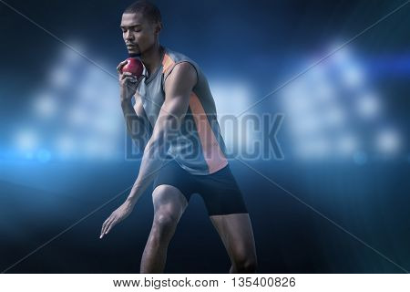 Athlete man concentrating during his shot put against composite image of spotlight