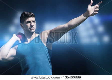 Front view of sportsman practicing shot put against composite image of spotlight