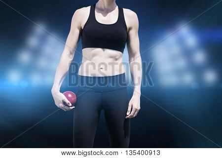 Sporty woman holding a red ball against composite image of spotlight