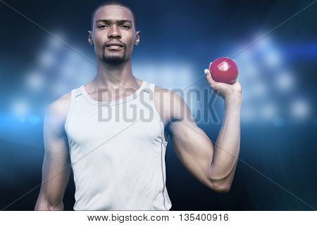 Portrait of serious sportsman is holding a shot put against composite image of spotlight