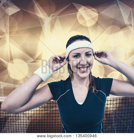 Female athlete wearing headband and wristband against lights as a background