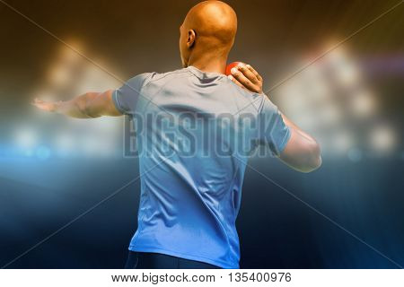 Rear view of sportsman is practising shot put against composite image of spotlight