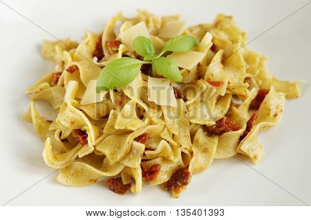 pasta with basil pesto, dried tomatoes and parmesan