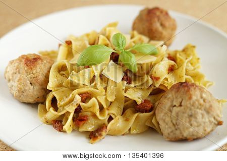 pasta with basil pesto, dried tomatoes, parmesan and meat balls