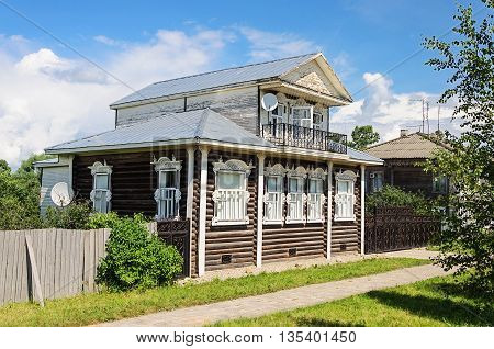 Beautiful country wooden house with mansard and carved windows Russia. Summer sunny day
