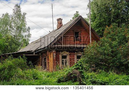 Old abandoned grassy log wooden house in russian village Vladimir region. Summer day
