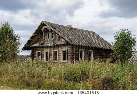 Old destroyed log wooden house in russian village Vologda region. Summer day