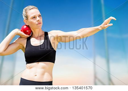Front view of sportswoman practising shot put against scenic view of blue sky