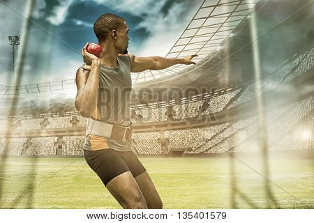 Rear view of sportsman practising shot put against view of a stadium