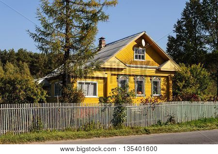 Yellow wooden house with decorated windows in russian village Yaroslavl region. Autumn sunny day