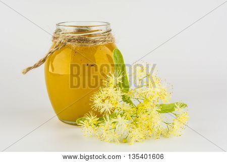 Glass jar with honey linden tie thread of jute with linden flowers on a white background