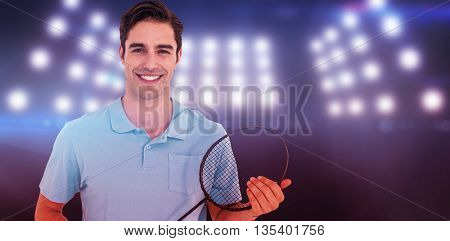 Portrait of badminton player holding badminton racket against composite image of spotlight