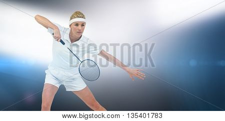 Badminton player playing badminton against spotlights