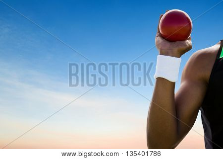 Close up of hand holding a shot against scenic view of blue sky