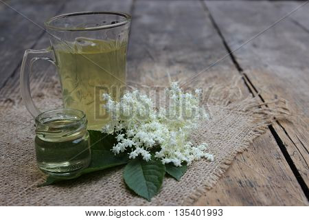 Glass cup with handle with tea and elderberry flowers.Jar with honey.