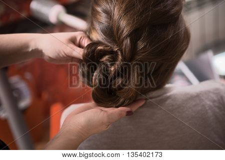 Closeup picture of beautiful lady sitting in chair and looking at mirror while hairdresser making braid in hairdressing salon.