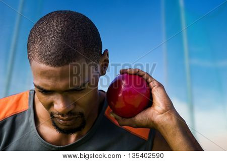 Portrait of sportsman practising shot put against scenic view of blue sky