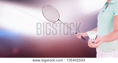 Pretty blonde playing badminton against spotlights
