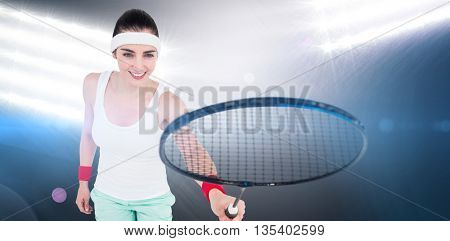 Female athlete playing badminton against spotlights