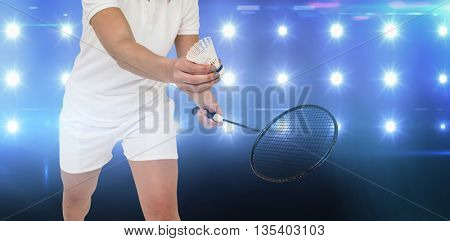 Female athlete holding a badminton racquet ready to serve against composite image of blue spotlight