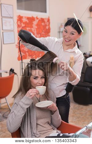 Beautiful lady drinking coffee while having her hair washed in hairdressing salon. Young woman looking at camera together with hairdresser.