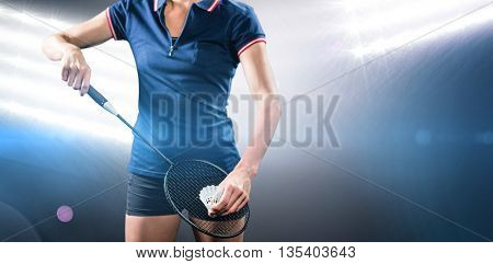 Badminton player holding a racquet ready to serve against spotlights