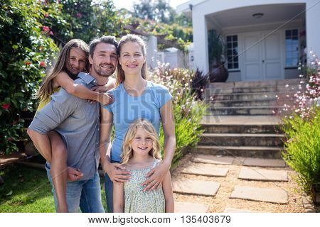 Portrait of family standing together on garden path