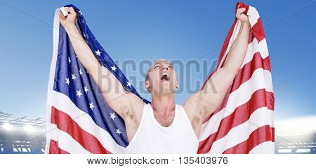Athlete posing with american flag after victory against large football stadium under bright blue sky