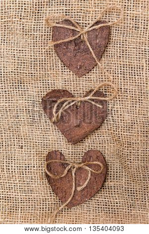 Three (3) decorative hearts made from tree bark on sackcloth, positioned in the middle of the photo. Hearts decorated with eco twine. Eco decor. St. Valentines greeting card idea. Handmade design.