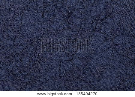Dark blue wavy background from a textile material. Fabric with natural texture closeup. Upholstery fabric pleated.