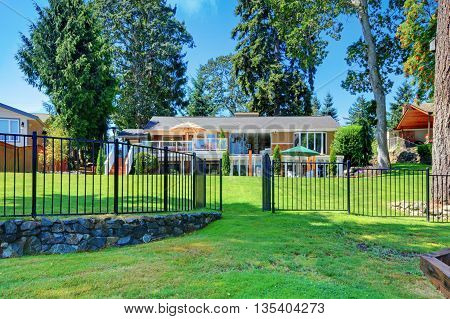 House Exterior. Back Yard With The Large House With Metal Fence.