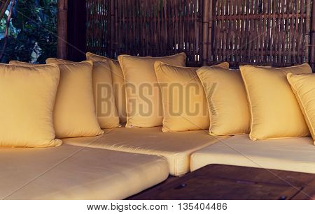 comfort, leisure and interior decoration concept - couch with pillows at hotel terrace