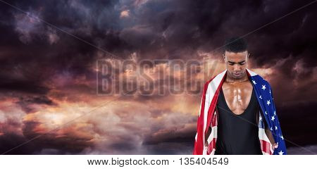 Athlete with american flag wrapped around his body against gloomy sky