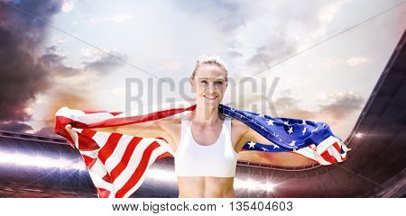 Portrait of smiling sportswoman posing with an american flag against composite image of stadium against cloudy sky