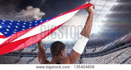 Athlete holding american flag against rugby stadium