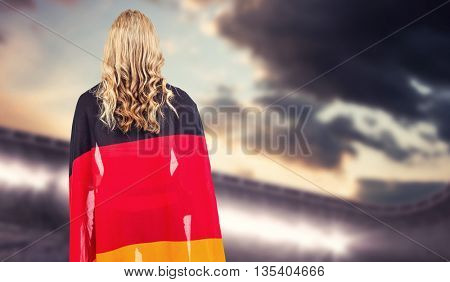 Athlete with german flag wrapped around her body against composite image of arena and cloudy sky